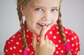 Little girl pointing to knocked out tooth