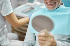 Dental patient smiling at himself in mirror, admiring partial dentures