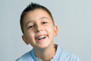 Portrait of smiling young boy with braces for children